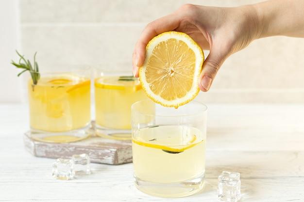 Vrouwelijke hand perst citroen in water, zomer vitamine drankje