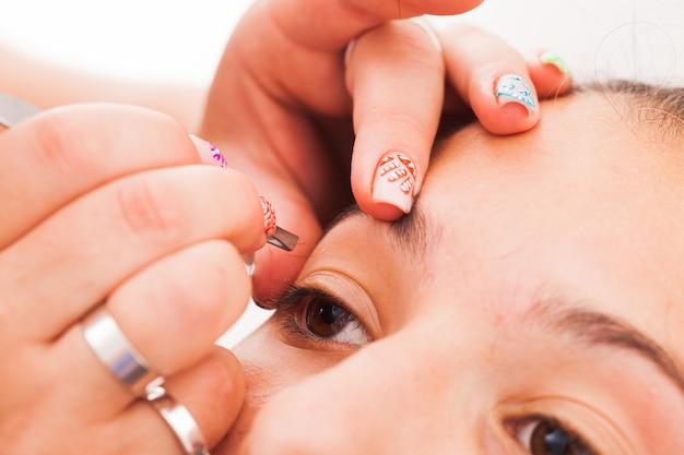 Vrouwelijke hand plukken menselijke wenkbrauwen close-up