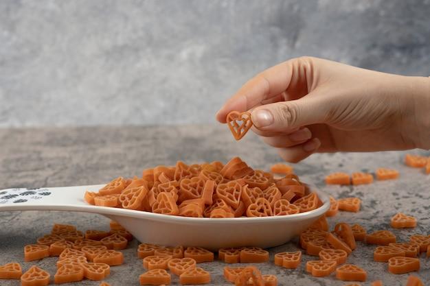 Vrouwelijke hand plukken rauwe macaroni van plaat op marmeren achtergrond