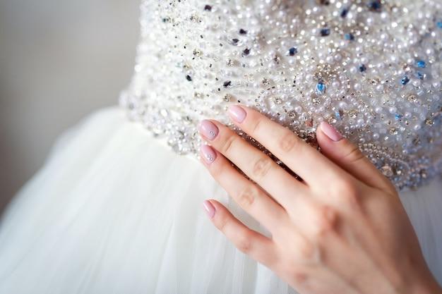 Vrouwelijke hand raakt de trouwjurk van de bruid met strass steentjes in de taille.