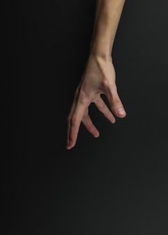 Vrouwelijke hand raakt iets op een zwarte achtergrond.