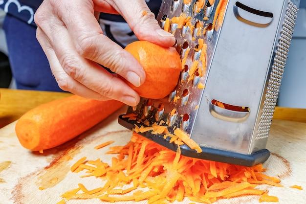 Vrouwelijke hand rasp verse fel oranje wortel op roestvrijstalen rasp