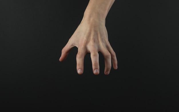 Vrouwelijke hand reikt naar iets op een zwarte achtergrond