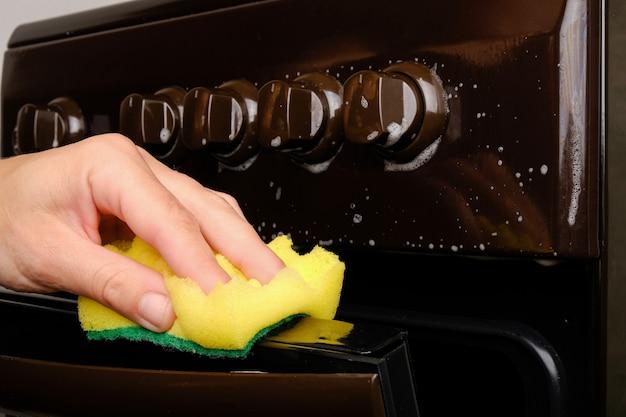 Vrouwelijke hand reinigt het gasfornuis met een spons met wit schuim en reinigt het oppervlak. hygiëne thuis, toestellen.