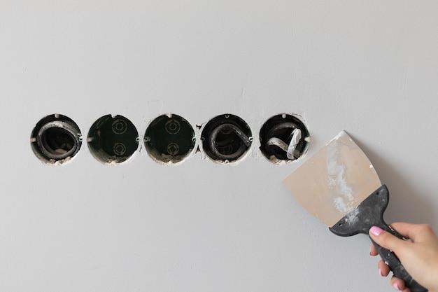 Vrouwelijke hand reinigt oude verf van de muren, doe-het-zelf-huisreparatie. hoge kwaliteit foto