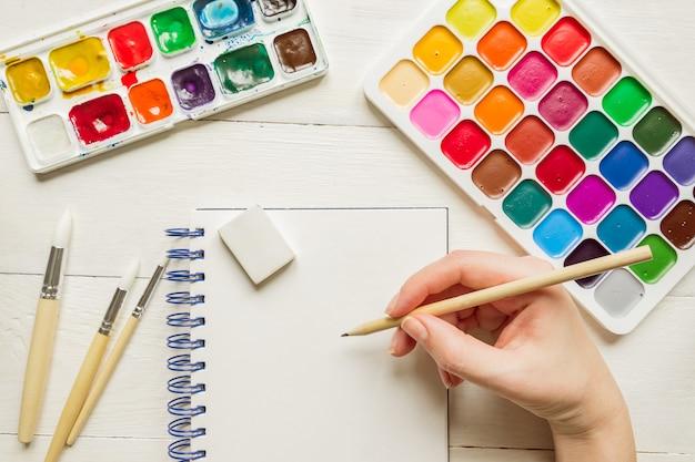 Vrouwelijke hand schetsen voor aquarel schilderen. aquarel verven en borstels, bovenaanzicht. creatieve artistieke mockup met copyspace