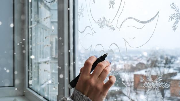 Vrouwelijke hand schilderij kerst herten geschilderd op vensterglas. kerst winter decor op het vensterglas. wit patroon van herten. sneeuw kunst maaswerk venster op vakantieseizoen. doe-het-zelf. hygge thuis
