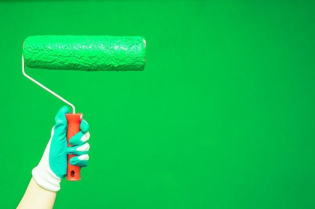 Vrouwelijke hand schildert muur met verfroller