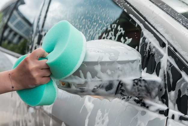 Vrouwelijke hand schoonmaak auto in dienst met hulpprogramma's zeep schuim en water. wassen auto