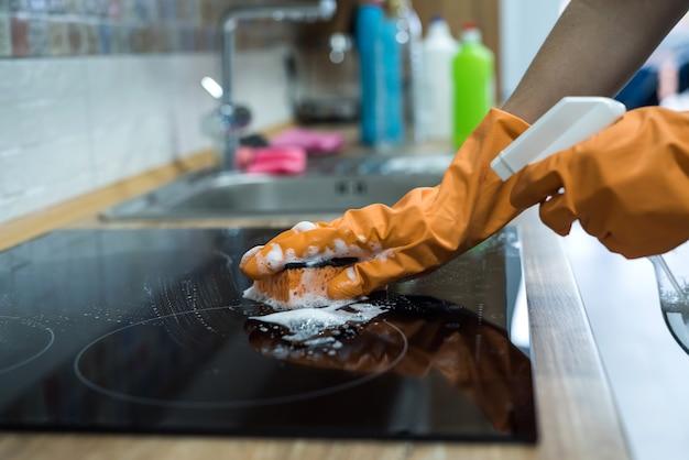 Vrouwelijke hand schoonmaken met spons en afwasmiddel moderne elektrische kookplaat van glas