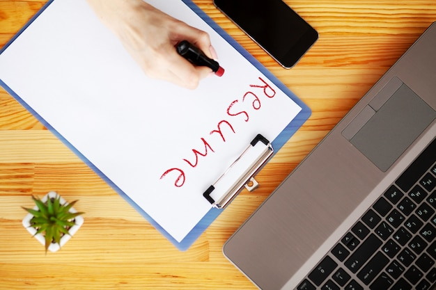 Vrouwelijke hand schrijft cv met lippenstift op wit vel papier