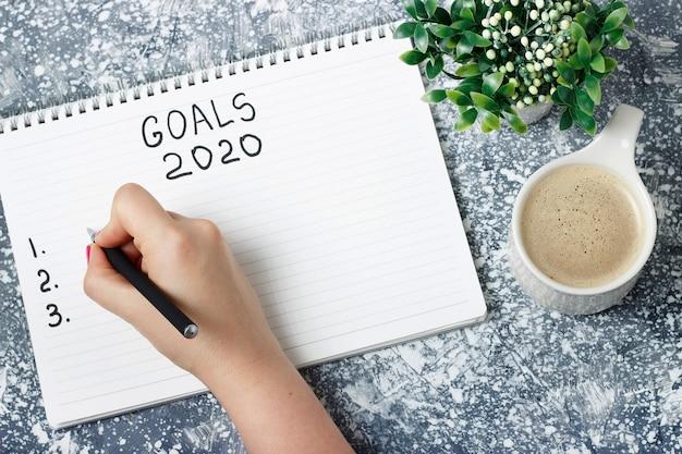 Vrouwelijke hand schrijft doelen in een notitieblok, planningsconcept