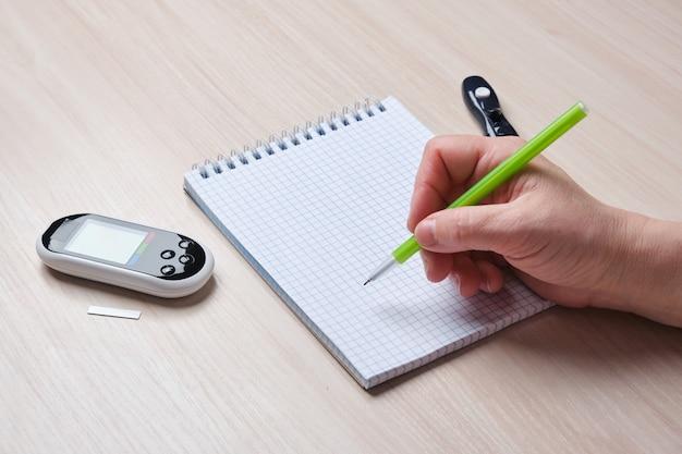 Vrouwelijke hand schrijft glucose meterstanden in notebook, diabetes en bloedsuikercontrole concept