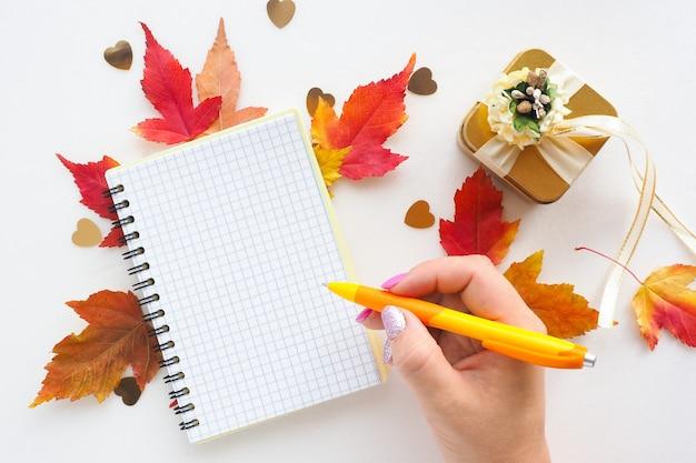 Vrouwelijke hand schrijft in een notitieboekje, rode en gele esdoornbladeren en een gouden geschenkdoos.