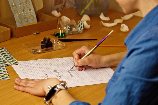 Vrouwelijke hand schrijft met de inkt met inkt de woorden dank en kalligrafie op een witboek