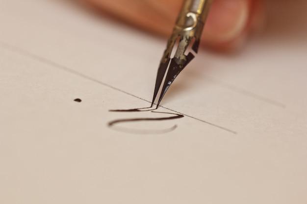 Vrouwelijke hand schrijft met de inkt met inkt op een vel wit papier met strepen.