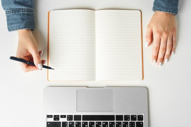 Vrouwelijke hand schrijven in een notitieblok op tafel met laptop, bovenaanzicht
