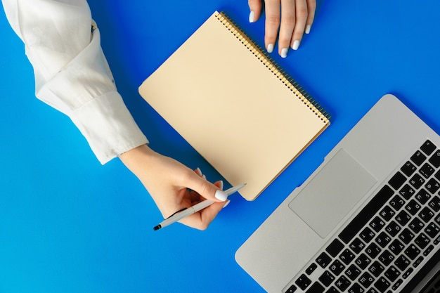 Vrouwelijke hand schrijven in een notitieblok op tafel met laptop, van bovenaf bekijken