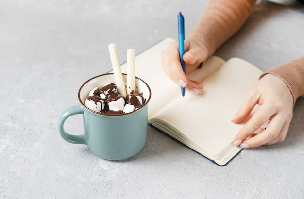 Vrouwelijke hand schrijven op een papieren notitieblok. warme chocolademelk mok met marshmallows, wafels en warme chocolademelk staan in de buurt.