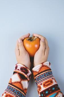 Vrouwelijke hand schuilt rijpe persimmon