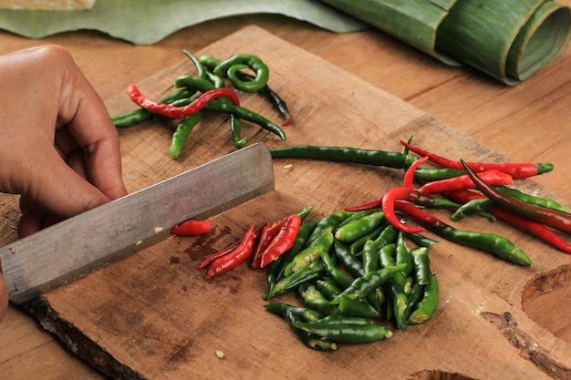 Vrouwelijke hand snijden gesneden chili peper op houten snijplank met mes