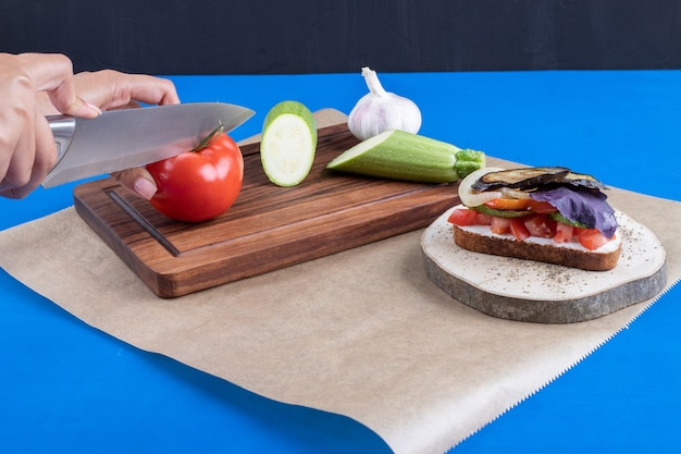 Vrouwelijke hand snijden verse tomaat op houten bord