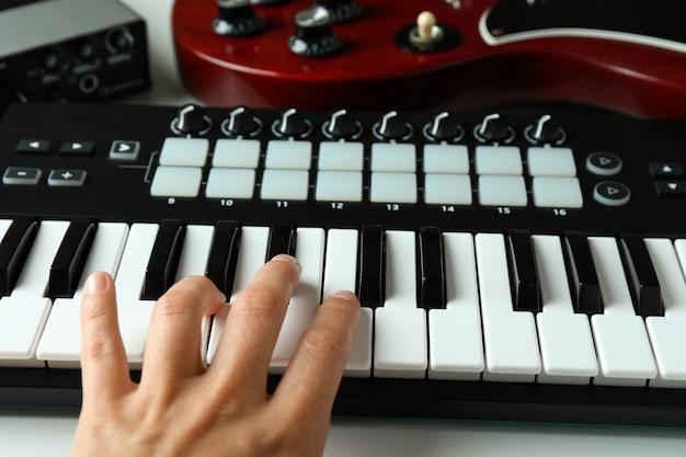 Vrouwelijke hand spelen op midi keyboard, close-up.