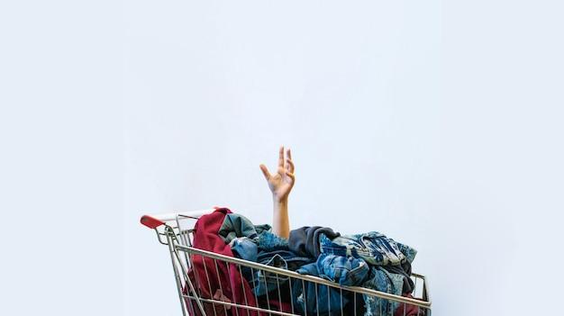 Vrouwelijke hand steekt uit winkelwagen vol kleren