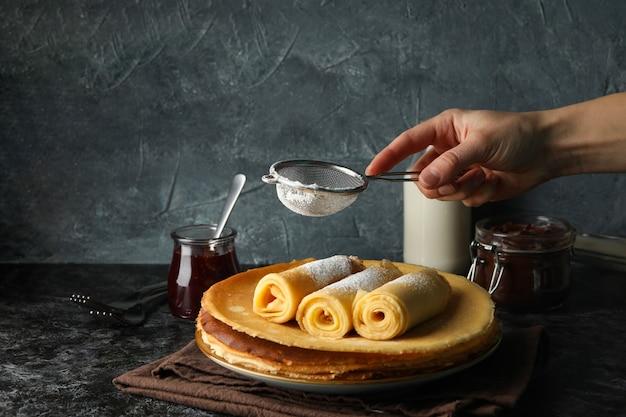 Vrouwelijke hand strooi suikerpoeder op crêpe broodjes