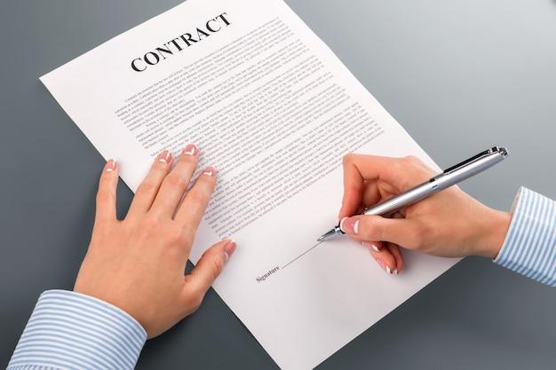 Vrouwelijke hand tekent leningscontract. vrouw hand ondertekening lening contract. ik heb geen keus. dit is zeer riskant.