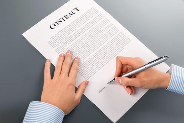 Vrouwelijke hand tekent samenwerkingscontract. dame die samenwerkingscontract ondertekent. we zullen sterker worden. twijfel nooit en aarzel nooit.
