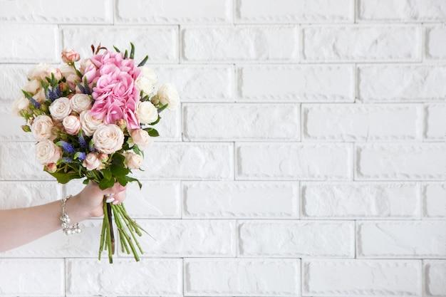 Vrouwelijke hand toon boeket met roze bloemen op witte bakstenen achtergrond. cadeau voor moeder of vrouw, bloemistenwerk, bruiloftsdecor, mooi boeketverkoopconcept