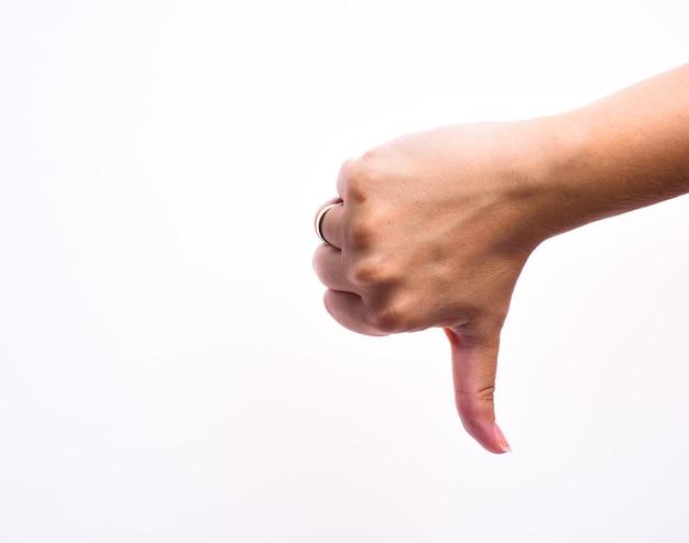 Vrouwelijke hand toont afkeer teken, duim naar beneden