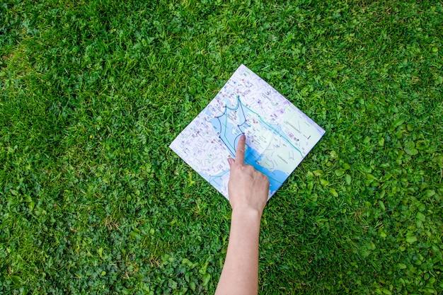 Vrouwelijke hand toont een vinger op een topografische kaart op het gras