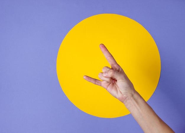 Vrouwelijke hand toont rock gebaar op paars met gele cirkel