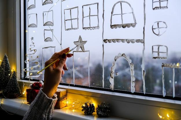Vrouwelijke hand trekt vakantie kerstversiering op vensterglas