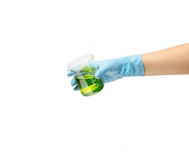 Vrouwelijke hand van een dokter in een veilige blauwe rubberen handschoen waarin de vloeistof een groen vaccin is, de ontwikkeling van medicijnen.