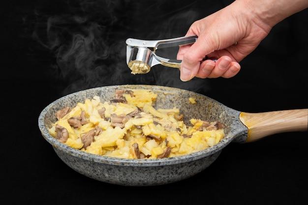 Vrouwelijke hand verplettert knoflook door een sapcentrifuge in een gebakken aardappel met champignons in een grijze met vlekken pan op een zwarte tafel