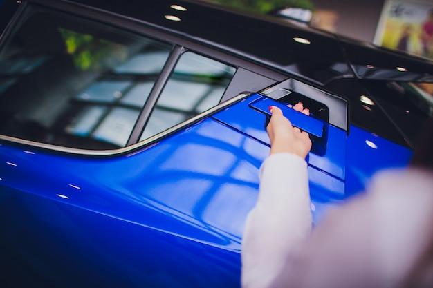 Vrouwelijke hand voor open achterdeur open auto. voor transport en automotive imago