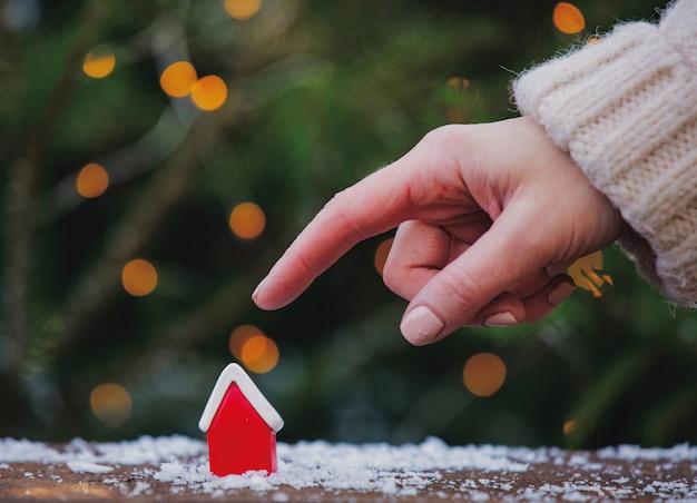 Vrouwelijke hand wijst naar een rood huis op de tafel
