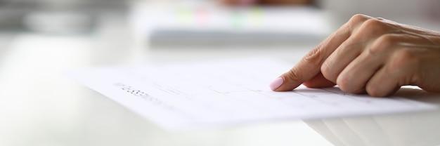 Vrouwelijke hand wijst vinger naar regel in document aan tafel in kantoor close-up. thuisonderwijs concept.