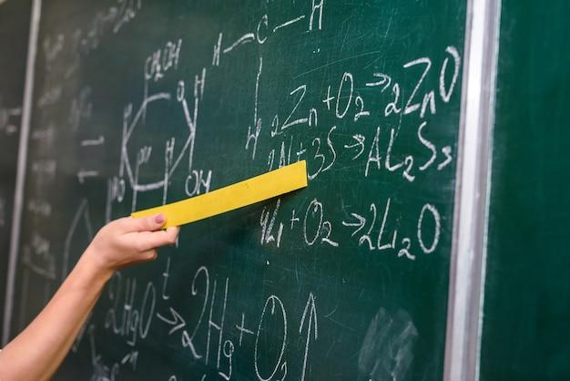 Vrouwelijke hand wijzend op chemische formule op blackboard close-up