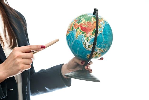 Vrouwelijke hand wijzend op wereldbol geïsoleerd