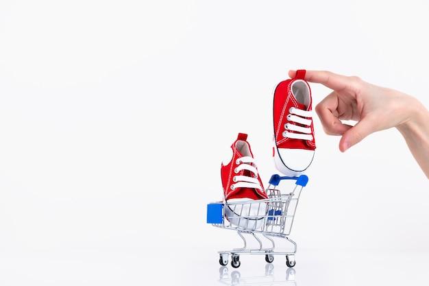 Vrouwelijke hand zet baby rode sneakers in het winkelwagentje geïsoleerd op een witte achtergrond. webwinkel in kinderschoenen. ruimte kopiëren.