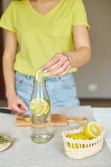 Vrouwelijke hand zet citroen in glazen fles, vrouw bereidt zich voor, maakt detox gezond water met citroen en rozemarijn, verse limonade in glas op een witte tafel thuis, zomerdrankje