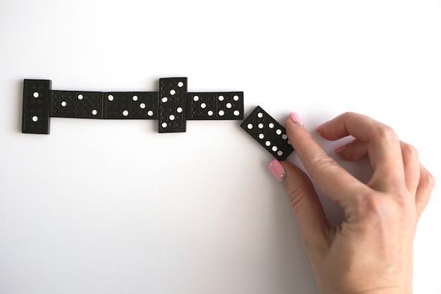 Vrouwelijke hand zet dominobot in een lijn, bovenaanzicht. speel dominostenen. bordspel