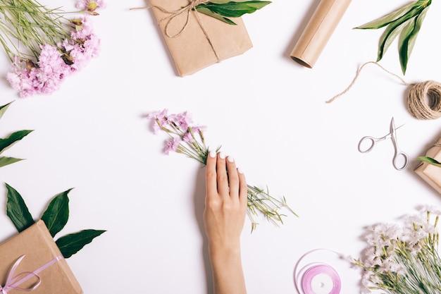 Vrouwelijke hand zet een boeket van roze bloemen op tafel