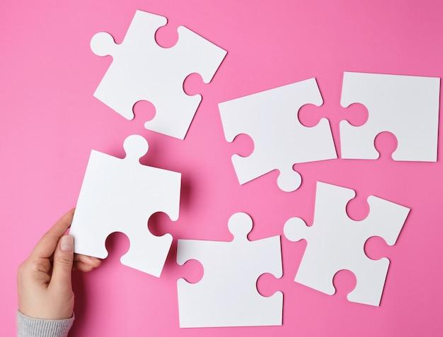 Vrouwelijke hand zet witte grote puzzels op roze