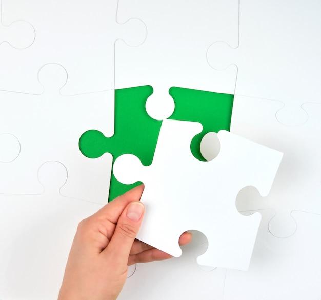 Vrouwelijke hand zet witte grote puzzels