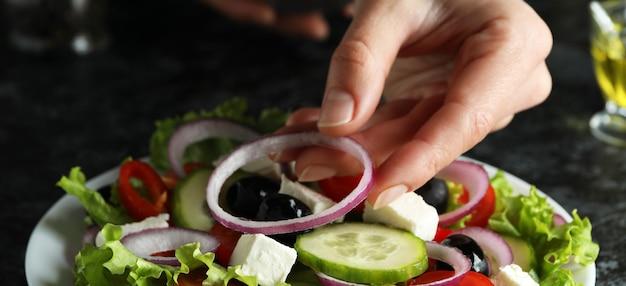 Vrouwelijke hand zette uien op griekse salade op zwarte smokey